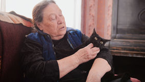 Portrait of old lady at home - old lady sits on sofa with black cat - close up Stock Images