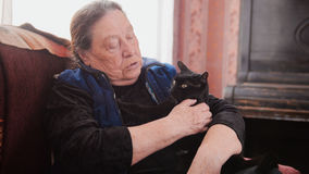 Portrait of old lady at home - senior woman sits on sofa with black cat - close up Stock Images