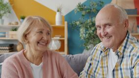 Portrait of old loving couple looking at each other and smiling then at camera