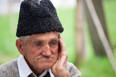 Portrait of an old man. Close up portrait of an old farmer over blurred green background Stock Photos