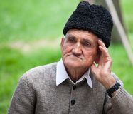 Portrait of an old man. Close up portrait of an old farmer over blurred green background Stock Images