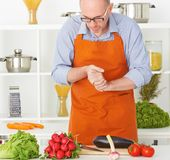 Portrait of an old man in an apron preparing to cut vegetables on a work surface in a kitchen Stock Photos