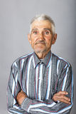 Portrait of an old man with arms folded. Over gray background Royalty Free Stock Photography