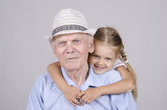 Portrait of an old man eighty years old with a four-year granddaughter Royalty Free Stock Image