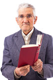 Portrait of an old man with glasses holding a red book Stock Photography