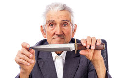 Portrait of an old man holding a knife and looking at camera Stock Photography