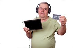 Portrait of old man listening to music in earphones using a tabl. Et with audiocassette in hand, . Outdated and new technology concept stock photo