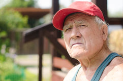 Portrait of an old man in a red baseball cap. An elderly man in a red baseball cap in the summer outdoors Royalty Free Stock Photo