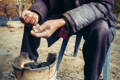 Portrait old man on rural of Thailand in winter season with the small fireplace - gain noise filter applied royalty free stock photos
