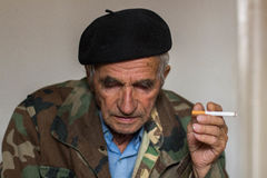 Portrait of an old man smoking cigarette. Indoors, close-up Royalty Free Stock Photo