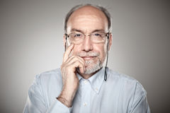 Portrait of old man taking glasses Royalty Free Stock Photo