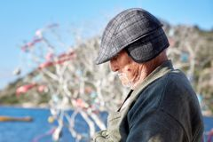Portrait of an old man wearing a cap at the age of 60s taking a nap near the seaside on a sunny day royalty free stock photo