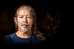 Portrait of old man. Portrait of wrinkles old man in hoary long hair character on black background royalty free stock photos