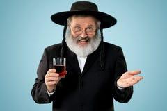 Portrait of old senior orthodox Hasdim Jewish man. With kosher wine at Jewish festival of Purim at studio. The purim, jewish, festival, holiday, celebration stock images
