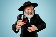 Portrait of old senior orthodox Hasdim Jewish man. With kosher wine at Jewish festival of Purim at studio. The purim, jewish, festival, holiday, celebration royalty free stock photos