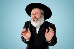 Portrait of old senior orthodox Hasdim Jewish man. With wooden Grager Ratchet at Jewish festival of Purim at studio. The purim, jewish, festival, holiday royalty free stock photo