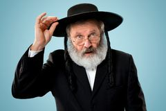 Portrait of old senior orthodox Hasdim Jewish man. With wooden Grager Ratchet at Jewish festival of Purim at studio. The purim, jewish, festival, holiday stock photography