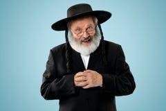 Portrait of old senior orthodox Hasdim Jewish man. With wooden Grager Ratchet at Jewish festival of Purim at studio. The purim, jewish, festival, holiday stock photos