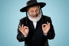 Portrait of old senior orthodox Hasdim Jewish man. With wooden Grager Ratchet at Jewish festival of Purim at studio. The purim, jewish, festival, holiday stock image
