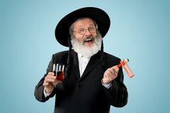 Portrait of old senior orthodox Hasdim Jewish man. With wooden Grager Ratchet at Jewish festival of Purim at studio. The purim, jewish, festival, holiday royalty free stock images