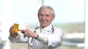 Portrait of old senior therapist is advising to use the drugs. The best medicine pills for you. Bright blurred windows background stock video footage