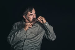 Portrait of an old Ukrainian peasant playing mouth organ in darkness Stock Images