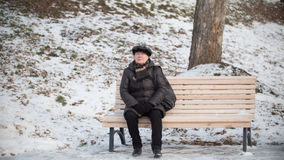 Portrait of the old woman on the bench at winter day in park. Horizontal Stock Photos