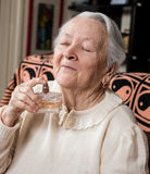 Portrait of  old  woman with bottle of perfume Stock Photography