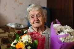 Happy old woman with a bouquet of flowers. royalty free stock photo