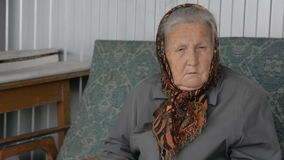 Portrait of an old woman in a brown kerchief stock video