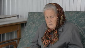 Portrait of an old woman in a brown kerchief stock video footage