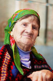 Portrait of old woman in coloured wear Stock Photography