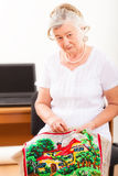 Portrait of an old woman engaged in needlework Stock Image