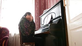 de3d37db17 Portrait of an old woman with glasses near piano. Close up stock video  footage
