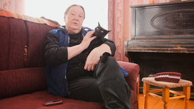Portrait of old woman home - senior lady sits on sofa with black cat Stock Image