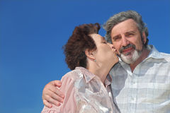 Portrait of old woman kissing man cheek. Blue sky Stock Photo