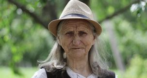 Portrait of an old woman with long gray hair in a straw hat outdoors. stock footage