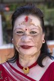 Portrait old woman with a pigmented spots on the face in the street. Pokhara, Nepal. POKHARA, NEPAL - OCTOBER 1, 2016 : Portrait old woman with a pigmented spots royalty free stock photos