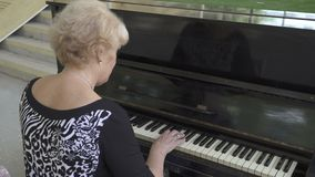 Portrait of an old woman playing the piano stock video footage