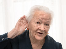 Portrait of old woman putting hand to her ear Stock Photos