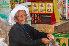 Portrait old woman serving. Mae Hong Son, Thailand - November 22nd 2011: Portrait of smiling old woman serving customer in the indoor market. . The market sells royalty free stock photo