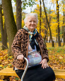 Portrait of old woman. Sitting on a bench  in autumn park Royalty Free Stock Photos