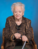 Portrait of old woman sitting with a cane Royalty Free Stock Image