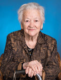 Portrait of old woman sitting with a cane Stock Images