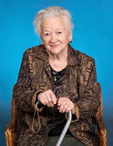 Portrait of old woman sitting with a cane Stock Photos