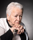 Portrait of old woman sitting with a cane Royalty Free Stock Photo