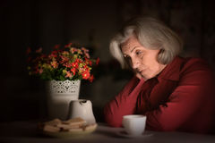 Portrait of an old woman sitting in the evening at home Royalty Free Stock Photos