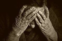 Portrait of an old woman. Toned portrait of an old woman with hands on face Royalty Free Stock Images