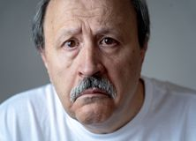 Close up portrait of sad old man face suffering from depression. Portrait of older adult senior man in pain with sad and exhausted face in human emotions facial stock photos