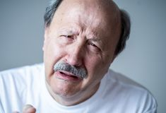 Close up portrait of sad old man face suffering from depression. Portrait of older adult senior man in pain with sad and exhausted face in human emotions facial stock photo